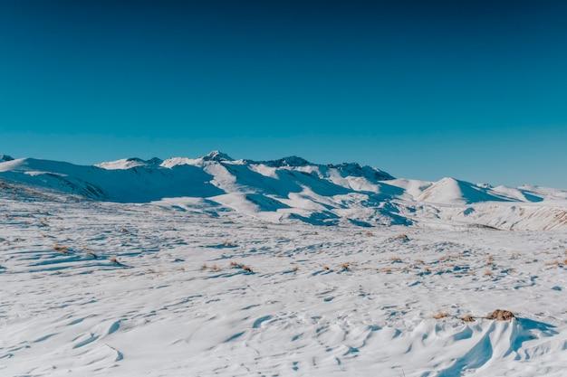 Paisagem de inverno nevado, montanhas, colinas e céu azul.