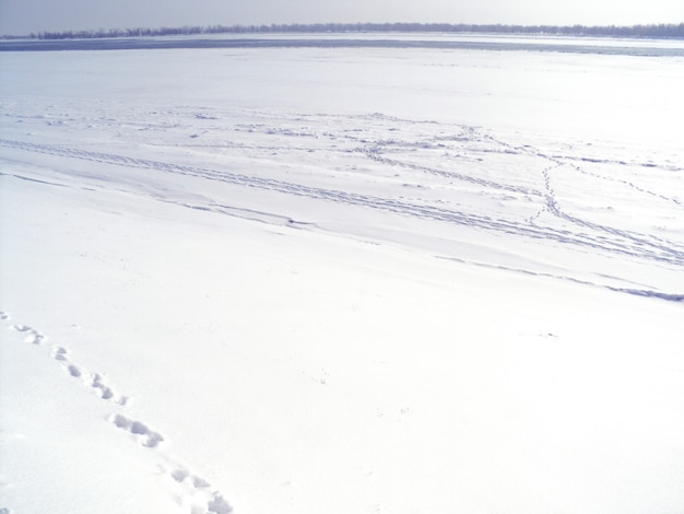Paisagem de inverno nevado nas margens de um rio congelado.