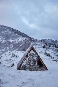 Paisagem de inverno. pequeno abrigo de madeira nas montanhas