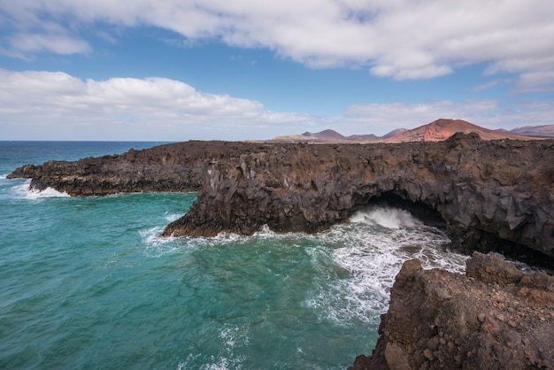 Paisagem de lanzarote. litoral de los hervideros, cavernas de lava, falésias e oceano ondulado.