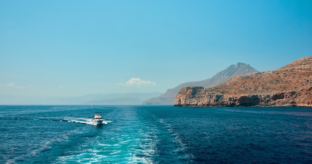 Paisagem de mar soberbamente brilhante, tirada de um barco em velocidade, tendo como pano de fundo falésias, um barco flutuante e um céu azul brilhante sem nuvens.