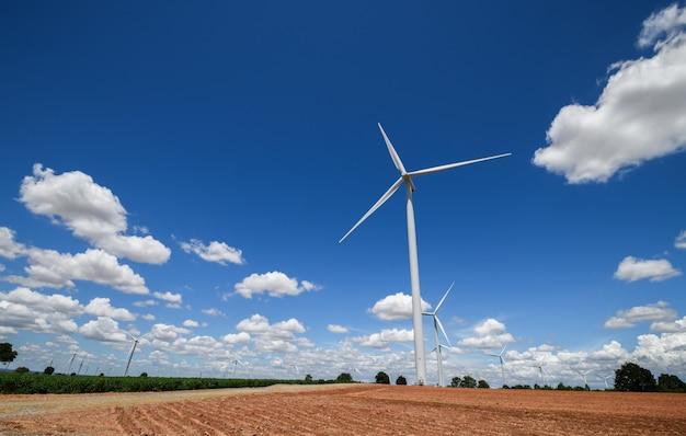 Paisagem de moinhos de vento para produção de energia elétrica com nuvens brancas e céu azul