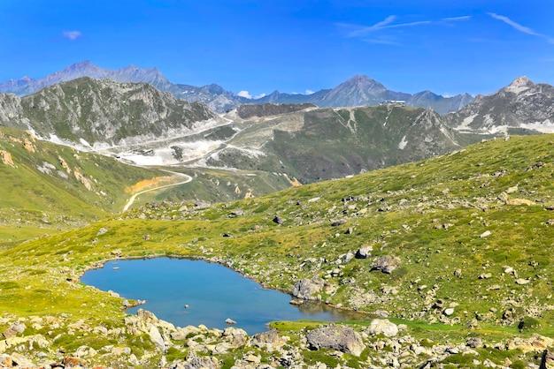 Paisagem de montanha alpina com um pequeno lago em um prado rochoso