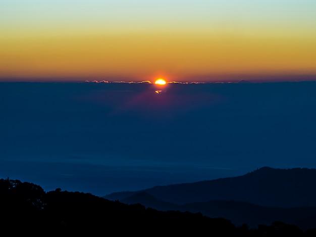 Paisagem de montanha com floresta e pôr do sol na hora do crepúsculo
