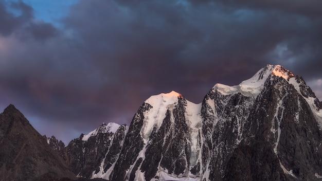 Paisagem de montanha de escuridão com grande montanha de neve iluminada pelo sol do amanhecer entre nuvens escuras. impressionante paisagem alpina com pináculo de alta montanha ao pôr do sol ou ao nascer do sol. grande geleira no topo em luz laranja.