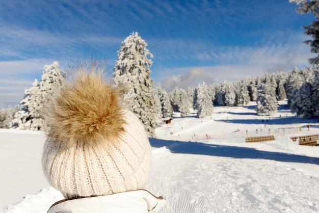 Paisagem de montanha do inverno com pessoa usando um boné