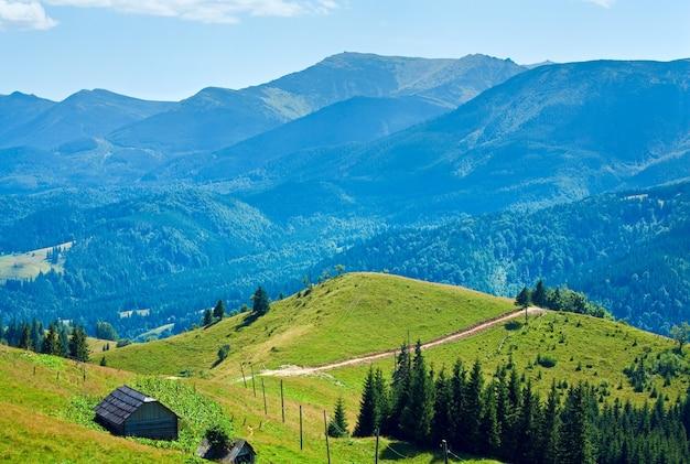 Paisagem de montanha enevoada de verão com celeiro em uma encosta, cárpatos, ucrânia