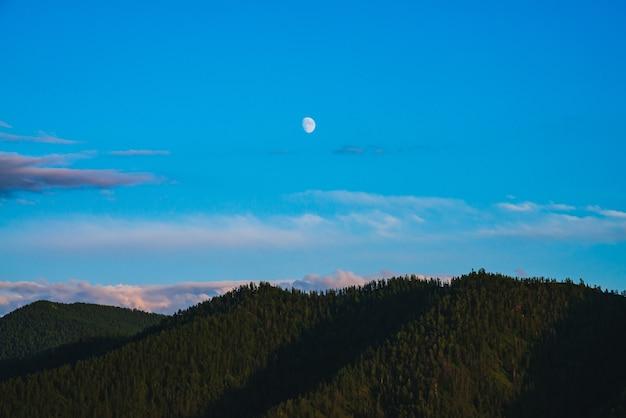 Paisagem de montanha mínima com grandes montanhas da floresta, sob o céu azul com nuvens violetas e lua no pôr do sol. bela paisagem ensolarada com floresta no topo de uma grande colina à luz do sol, sob a lua e nuvens lilás.