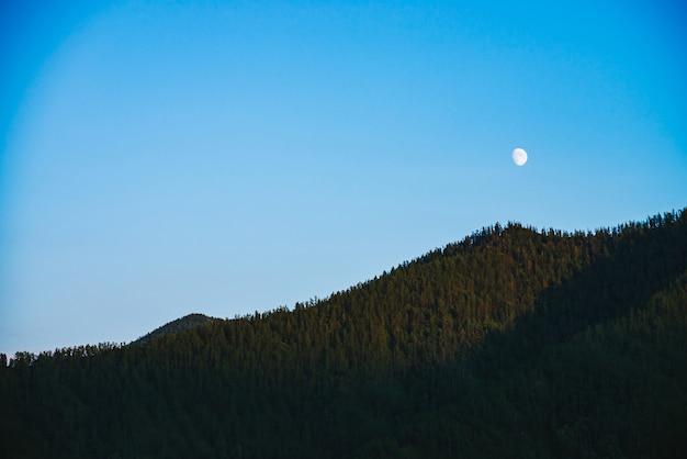 Paisagem de montanha mínima com montanhas de grande floresta, sob o céu azul claro com lua.