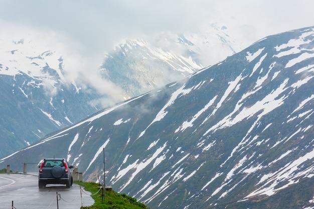 Paisagem de montanha nublada de primavera (oberalp pass, suíça). o modelo do carro está irreconhecível.