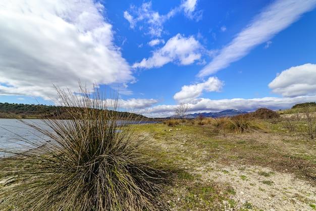 Paisagem de montanha verde com lago azul, estrada de terra e grandes nuvens no céu, atmosfera de primavera. guadalix madrid. europa.