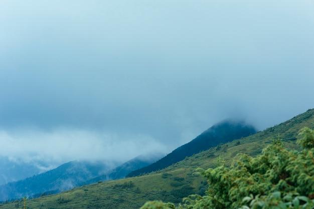 Paisagem de montanha verde contra o céu nublado
