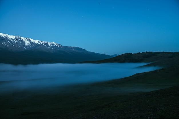 Paisagem de montanhas atmosféricas com nevoeiro denso e grande cordilheira de neve sob o céu crepuscular. cenário alpino com grande cume de montanhas nevadas, espesso nevoeiro à noite. rochas nevadas acima das nuvens ao entardecer.