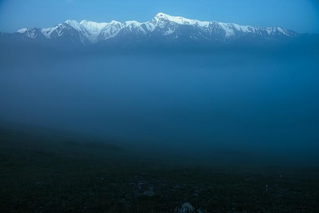 Paisagem de montanhas atmosféricas com nevoeiro denso e grande topo de montanha de neve sob o céu crepuscular. cenário alpino com grandes montanhas nevadas, sobre espesso nevoeiro durante a noite. auge da neve alta acima das nuvens ao entardecer.