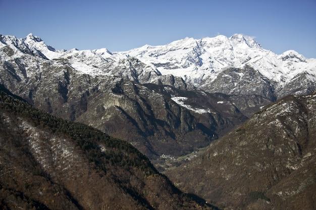 Paisagem de montanhas cobertas de árvores e neve sob a luz do sol e um céu azul