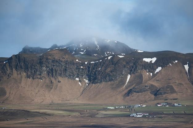 Paisagem de montanhas cobertas de neve e grama sob um céu nublado na islândia