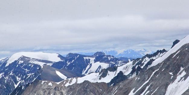 Paisagem de montanhas cobertas de neve sob um céu nublado durante o dia