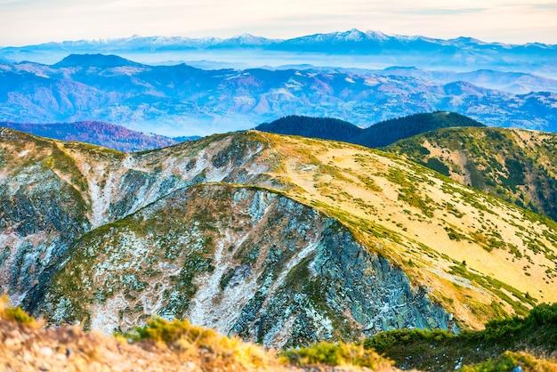 Paisagem de montanhas com vários terrenos e céu ao pôr do sol