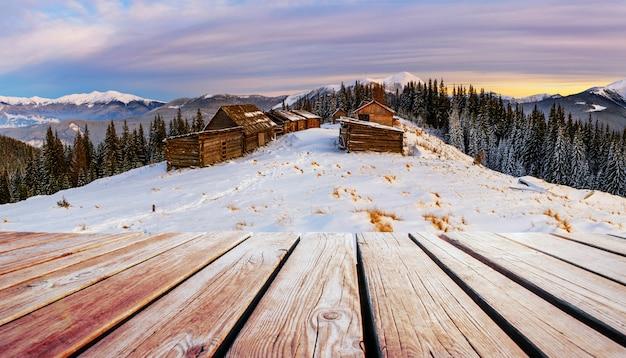 Paisagem de montanhas de inverno com um bosque nevado e uma cabana de madeira e mesa gasto.