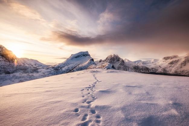 Paisagem de montanhas de neve com pegada na neve ao nascer do sol