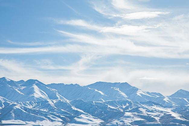 Paisagem de montanhas nevadas com céu azul e nuvens