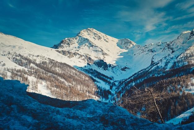 Paisagem de montanhas rochosas cobertas de neve sob o sol em sestriere, na itália