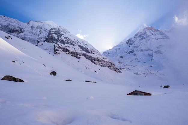 Paisagem de montanhas rochosas cobertas de neve sob um céu nublado