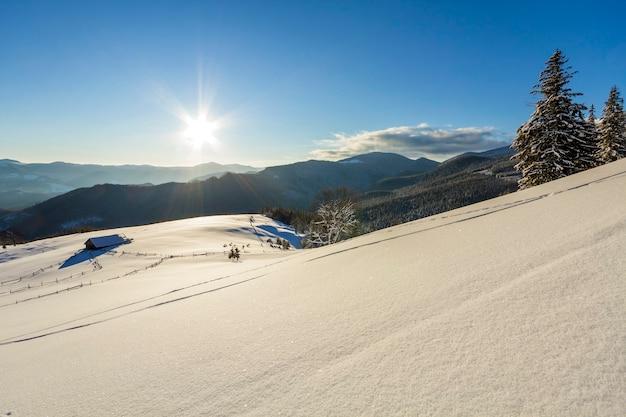 Paisagem de natal de inverno do vale da montanha em um dia ensolarado e gelado. velha cabana de pastor abandonada de madeira na neve limpa profunda branca, cume da montanha escura lenhosa, sol brilhante no fundo do espaço da cópia do céu azul.