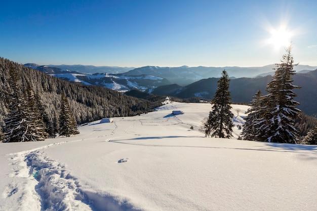 Paisagem de natal de inverno do vale da montanha em um dia ensolarado e gelado. velha cabana de pastor de madeira abandonada na neve limpa profunda branca, cume da montanha escura lenhosa, sol brilhante no fundo do espaço da cópia do céu azul.