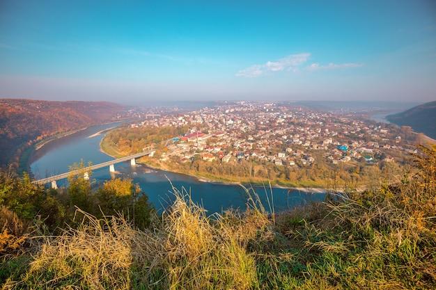Paisagem de natureza urbana incrível. fantástica vista aérea panorâmica da cidade de zalishchyky e do meandro do rio dniester em um dia ensolarado de outono. parque nacional dniester canyon, oblast de ternopil, ucrânia