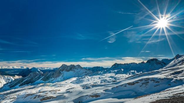 Paisagem de neve fantástica com vista para a montanha íngreme e luz solar cintilante
