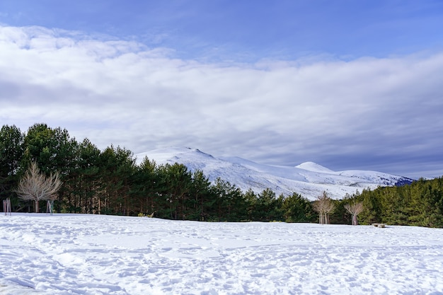 Paisagem de neve na montanha de madrid com sol, céu azul e alta montanha. morcuera.
