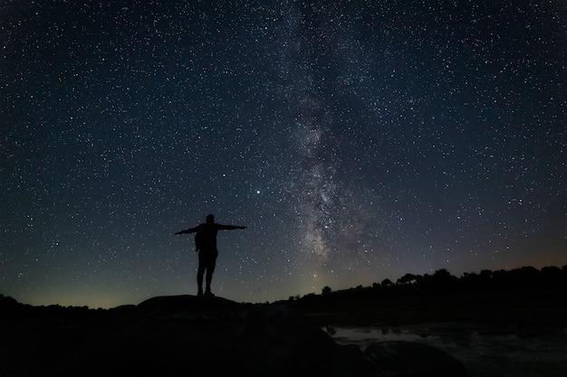 Paisagem de noite estrelada com silhueta humana