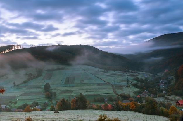 Paisagem de outono aldeia na encosta. floresta no nevoeiro nas montanhas à noite luz da lua cheia