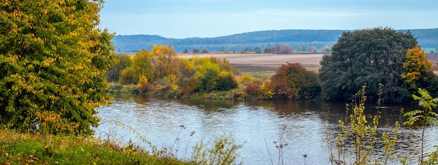 Paisagem de outono. árvores coloridas à beira do rio no outono em um dia ensolarado
