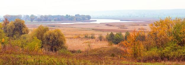 Paisagem de outono com árvores coloridas em uma vasta planície e um rio à distância, panorama