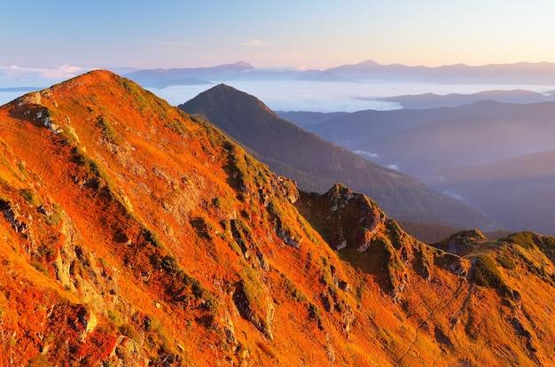 Paisagem de outono com grama vermelha nas encostas da montanha. manhã ensolarada nas montanhas