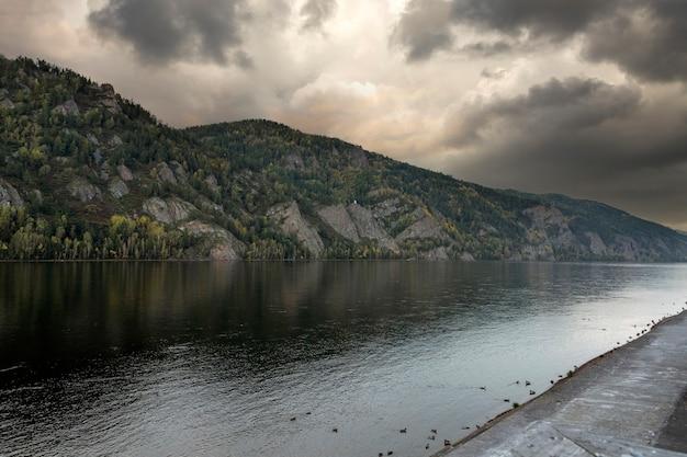 Paisagem de outono com rio, céu nublado e montanhas cobertas de floresta