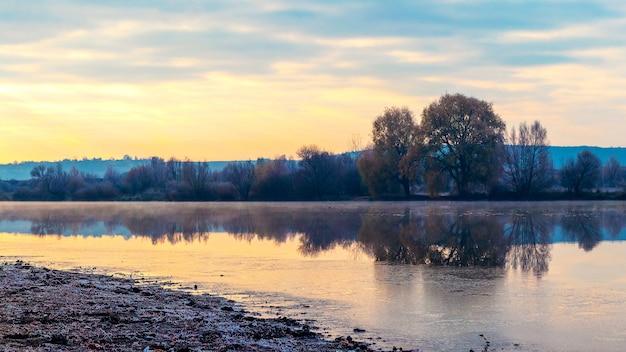 Paisagem de outono com um céu pitoresco ao amanhecer, que se reflete no rio