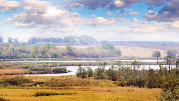 Paisagem de outono com um rio, árvores à beira do rio e nuvens pitorescas por onde os raios do sol penetram