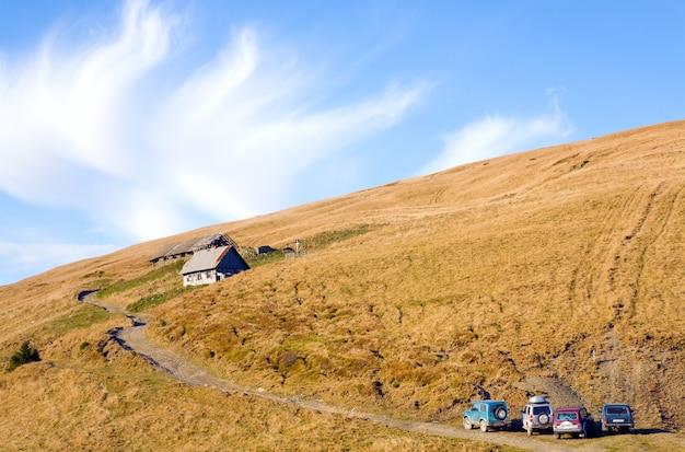 Paisagem de outono das montanhas dos cárpatos (ucrânia) com fazenda de criação de gado e estrada secundária com alguns carros 4wd.