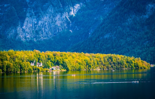 Paisagem de outono ensolarada do lago e do castelo branco na floresta hallstatt