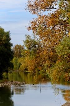 Paisagem de outono idílica cênica colorida em uma margem do rio com árvores, refletindo sobre a água