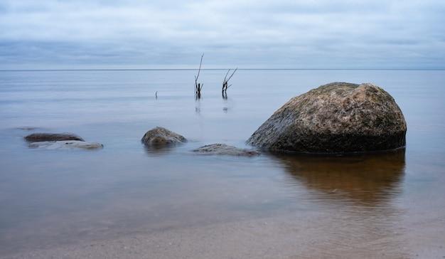 Paisagem de outono no reservatório de rybinsk, rússia. algumas pedras na água. céu nublado