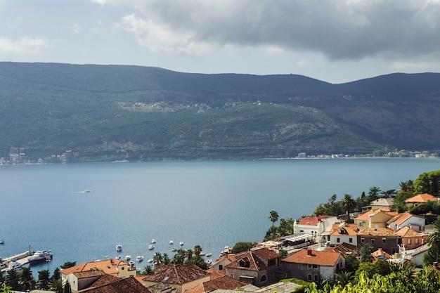 Paisagem de plano urbano em clima quente e ensolarado na cidade de kotor. a cidade é cercada por montanhas e rochas, ao pé das quais o mar está transbordando.
