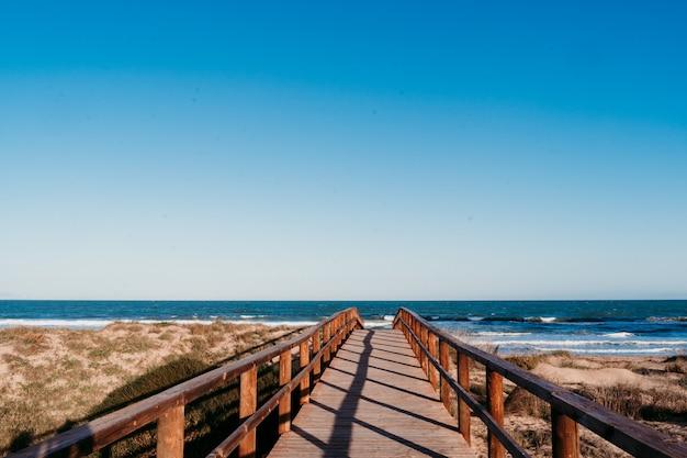 Paisagem de praia ao pôr do sol. caminho da ponte de madeira. céu azul