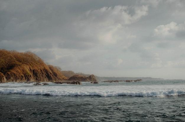Paisagem de praia na costa rica. onda e céu azul rochas