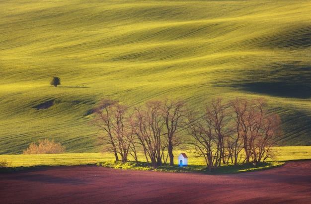 Paisagem de primavera com capela incrível em campos verdes ao pôr do sol