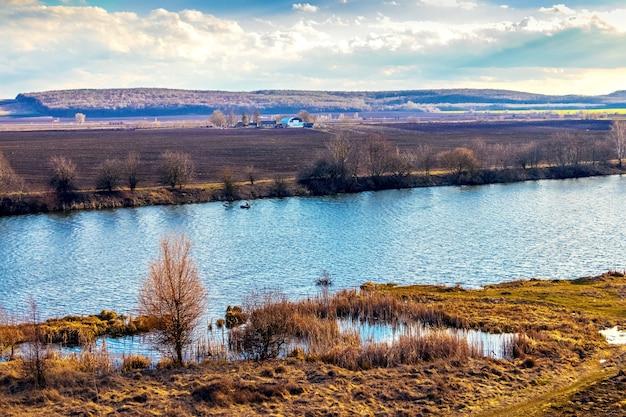 Paisagem de primavera com rio, campo e juncos secos na costa