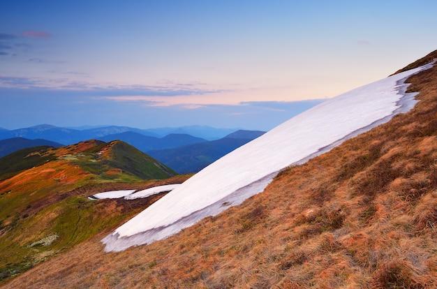 Paisagem de primavera nas montanhas. snowfield em uma encosta de montanha